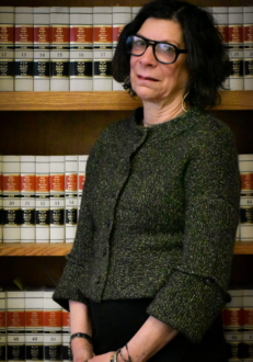Dark haired woman with glasses in front of bookcase