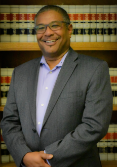 smiling Black man in front of bookcase