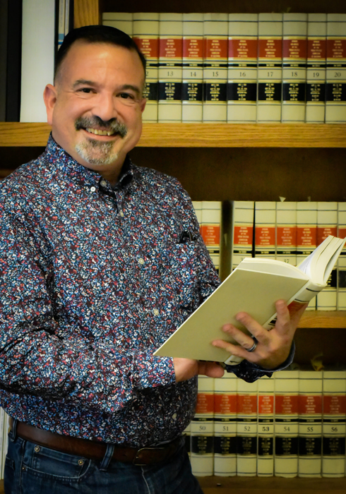 smiling latino man with goatee holding book in front of bookcase