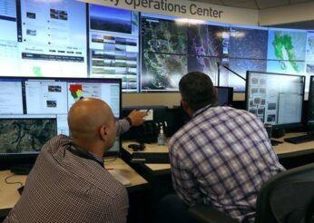 men sitting at computer control booth in energy operations center